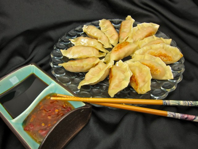 Cooked potstickers with dipping sauces